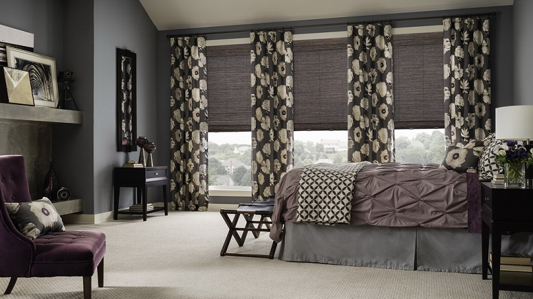 Three windows with patterned drapes and purple shades inside of a master suite.